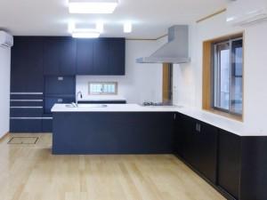 黒いメラミン扉、白い人大天板の壁付け型対面キッチン。